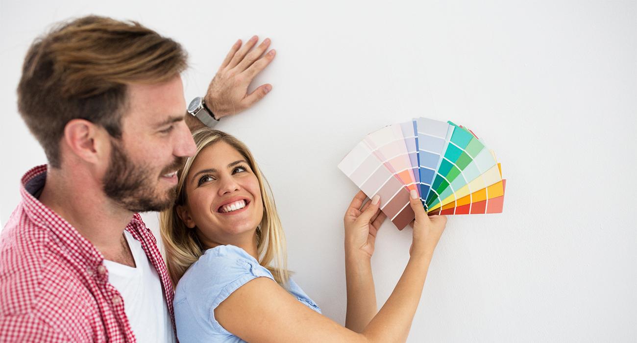 Pärchen berät sich für die Farbwahl des neuen Wohnzimmers